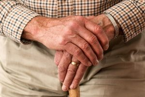 A senior hand with a wedding ring.