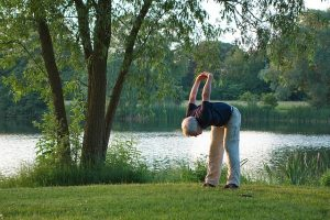 A senior is practicing yoga in the park