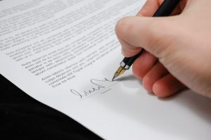 Signing paper. When it comes to international relocations you need to make sure that everything is ready.