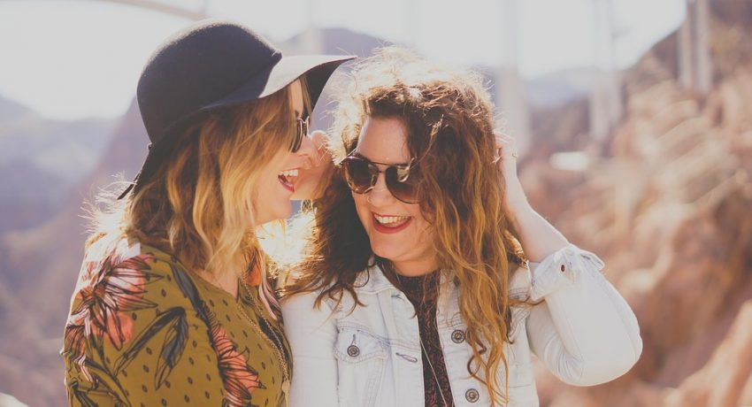 two girls laughing because they succeeded in making friends after relocation