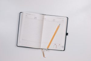 Open planner with a pencil