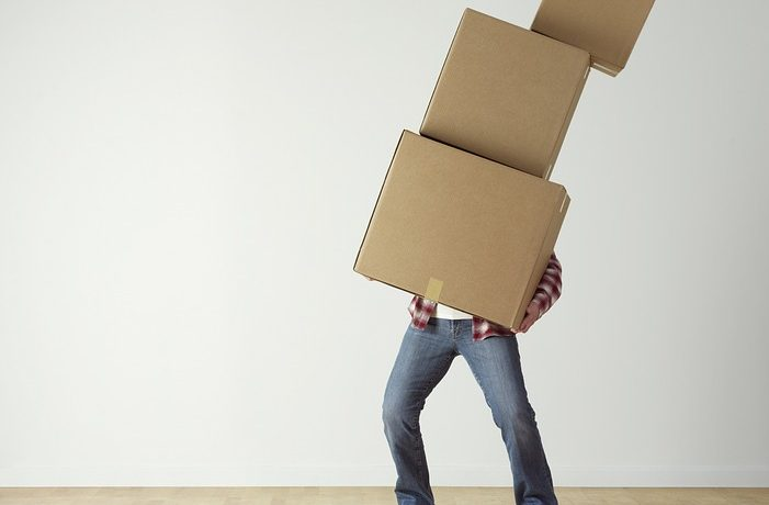 A person carrying boxes trying to categorize your household items before the move