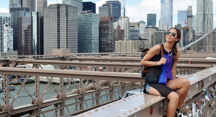 A girl smiling while sitting on an NYC bridge.