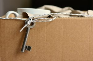 A cardboard box and a key hanging over its edge.