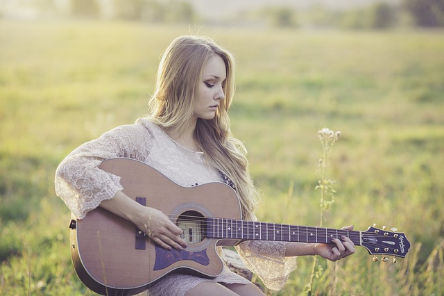 A girl playing a guitar outside