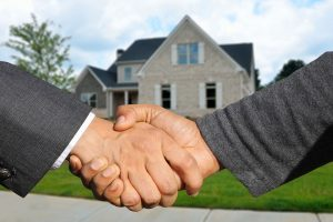 A realtor and a buyer shaking hands in front of a house