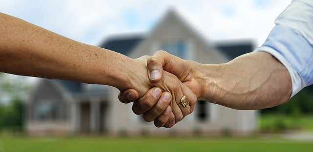 Shaking hands after buying a house and moving to Arlington, TX