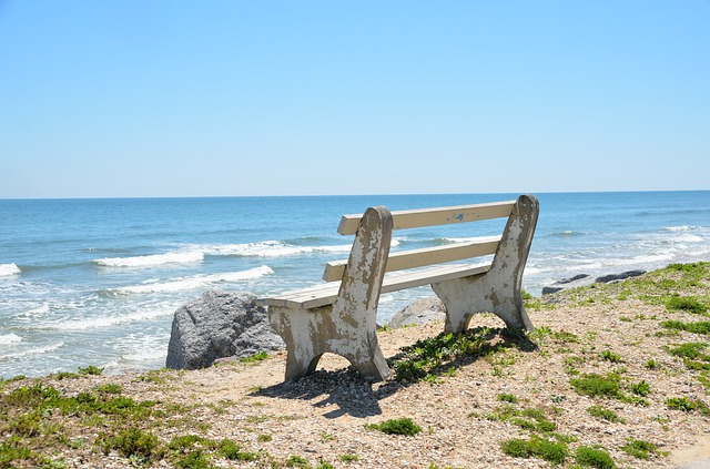 A white bench on a beach, representing cities in Florida with sunny weather.