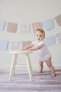 There is a baby standing and leaning his hands on a chair. Furniture safety is one of the points from our baby proofing checklist for before baby can crawl.