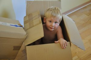 A small boy in a cardboard box.