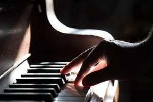 A hand playing a piano.