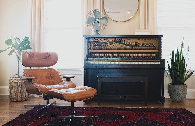 A chair next to a piano.