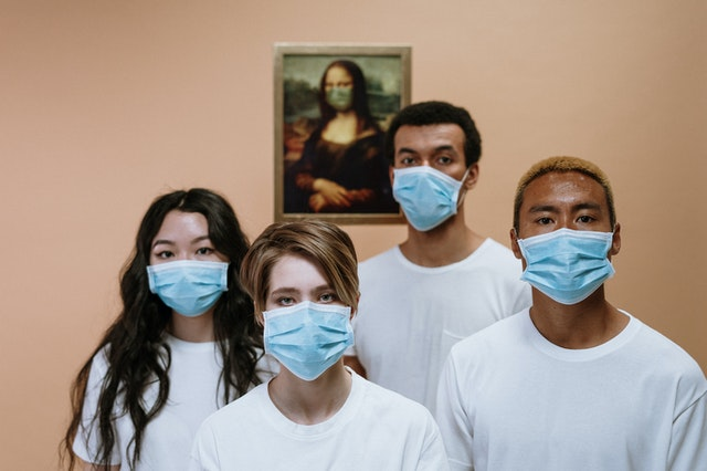There is a group of four people wearing face masks.