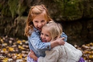 Two girls hugging each other.