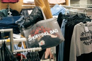 A woman carrying a shopping bag in a shop.