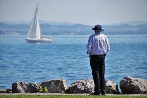 A senior looking at the lake.
