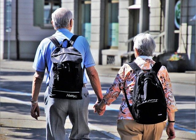 A senior couple walking and thinking about selling a senior-owned home.
