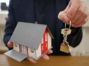 A man holding a key ring and a small model house in his hands.