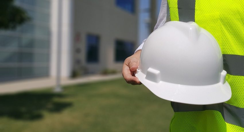 A construction worker holding a white helmet.