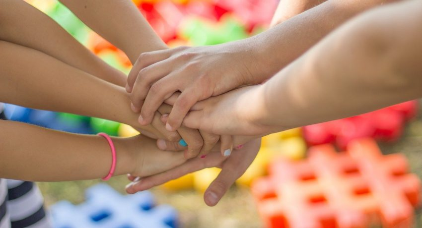 A group of friends joinging hands together.