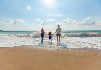 A family enjoying a beach scene by the ocean.