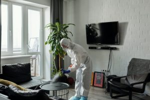 person in white protective suite cleaning in the living room